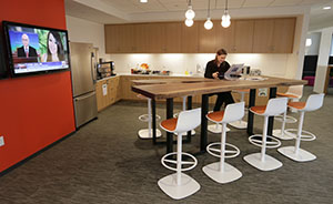 "Accenture's ""café"" has a coffee bar, a small kitchen and a long, walnut table with barstools."
